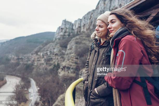 Female travelers standing on high terrace in the rocks and looking at the canyon