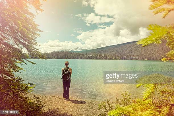 female traveller looking over lake in the sun