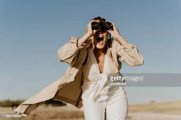 female traveller looking through binoculars - white jumpsuit stock pictures, royalty-free photos & images