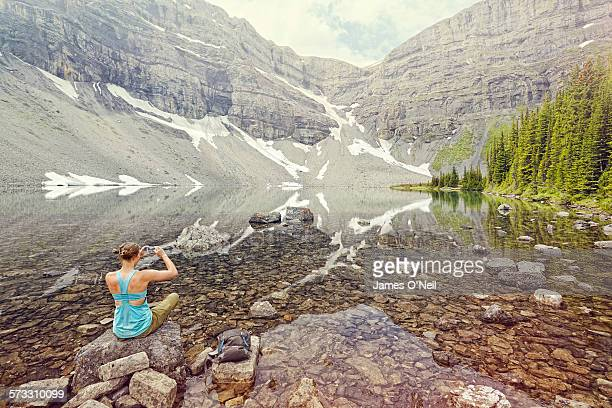 female traveller photographing alpine lake