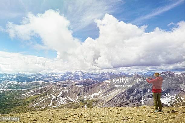 Female traveller photographing mountain range