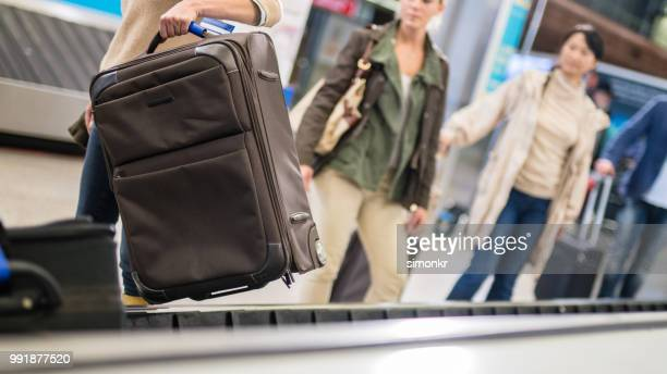 Female traveller picking up suitcase from baggage claim line