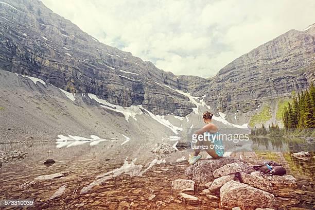 Female traveller resting at alpine lake