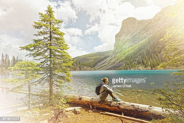 female traveller sitting viewing alpine lake