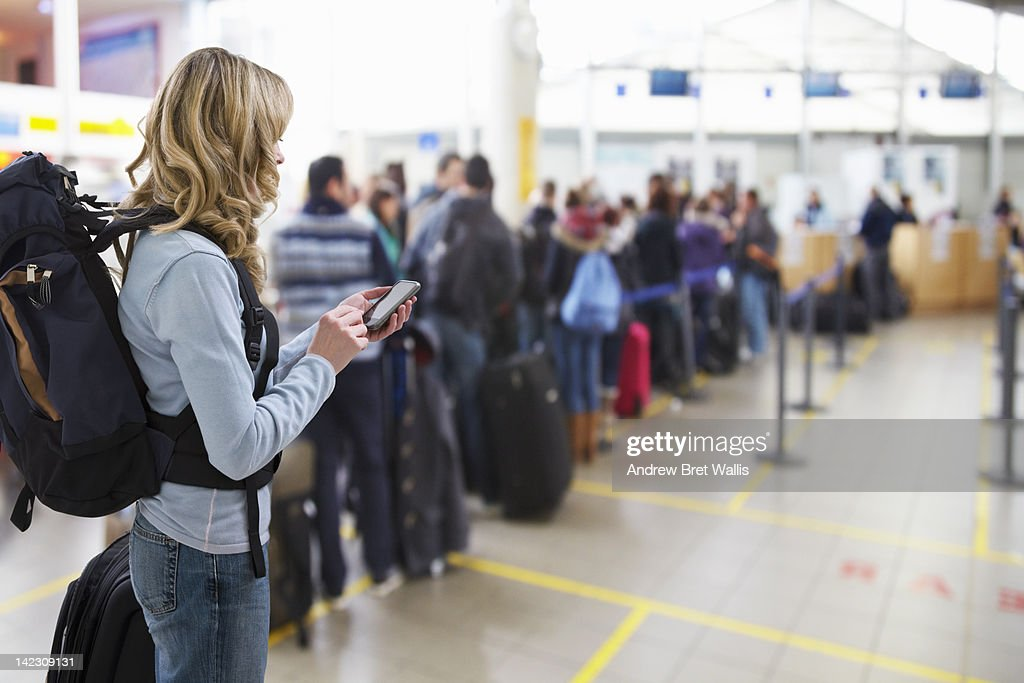 female traveller texting at airport check-in desk : Stock Photo