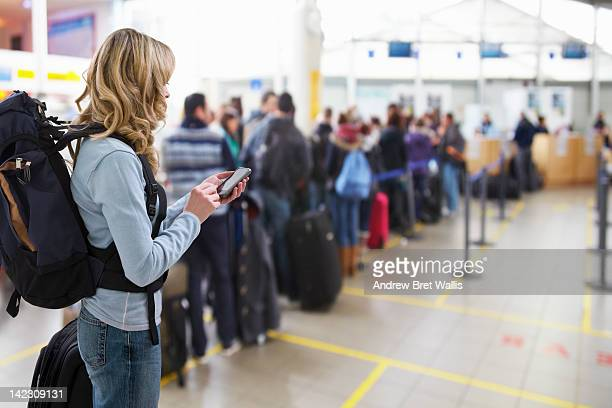 female traveller texting at airport check-in desk - lining up stock pictures, royalty-free photos & images