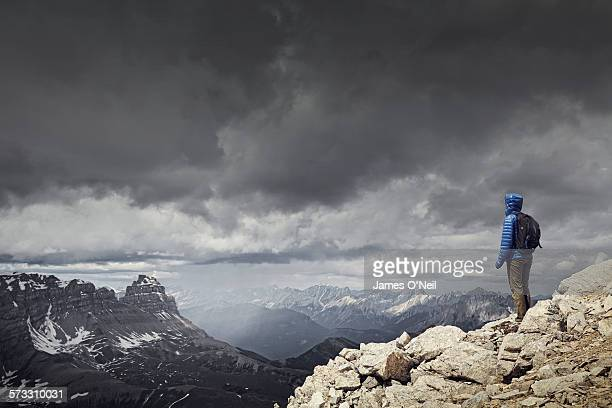 female traveller watching storm over mountains