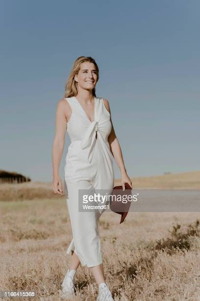 female traveller with straw hat - blue jumpsuit stock pictures, royalty-free photos & images