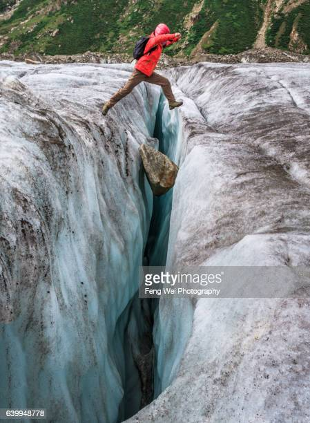 Female Trekker Jump Over Crevasse On Biafo Glacier, Mango To Baintha, Biafo Hispar Snow Lake Trek,  Central Karakoram National Park, Gilgit-Baltistan, Pakistan