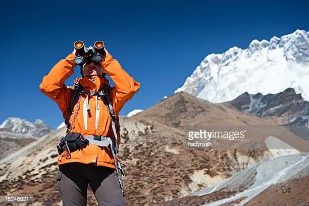 Female trekker looking through binoculars, Lhotse in background