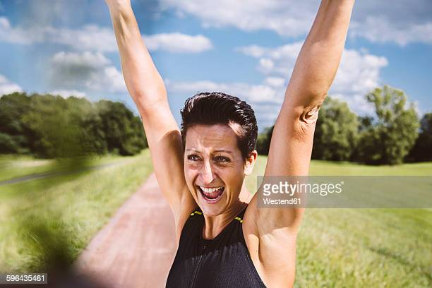 Female triathlete cheering with arms up