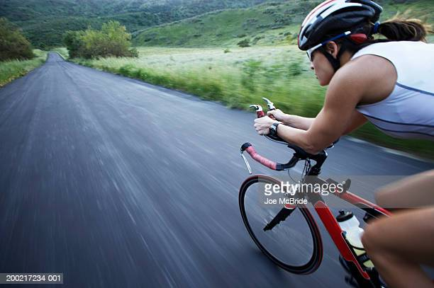 female triathlete cycling on country road - sportlerin stock-fotos und bilder