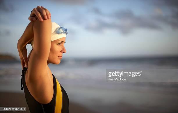 Female triathlete doing stretching exercise on beach