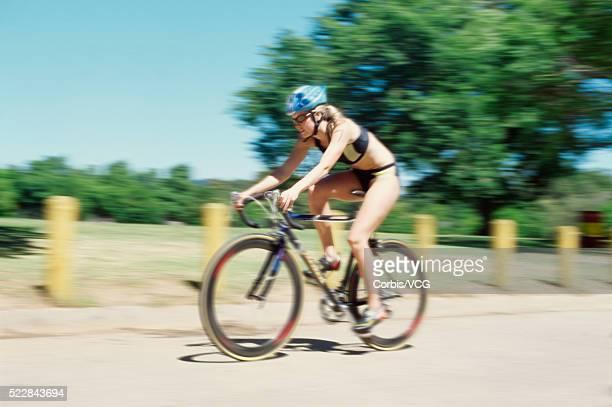 female triathlete riding a bicycle - ブラトップ ストックフォトと画像