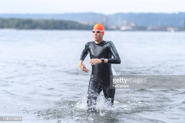 A female triathlete rushing out of the water