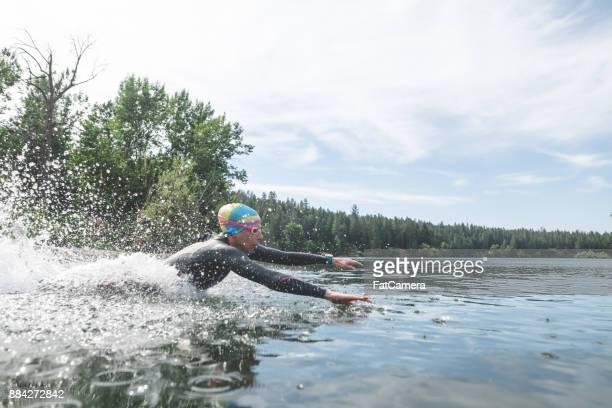 Kvinnliga triathlon atlet dykning i vattnet