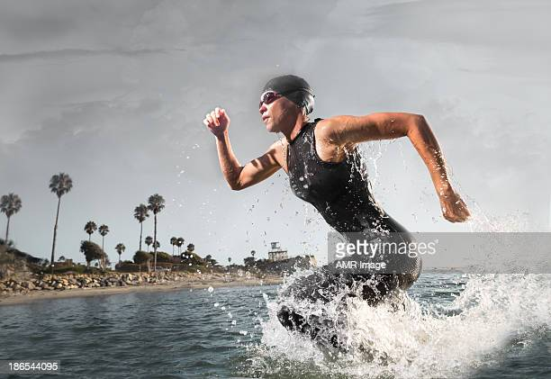 female triathlon athlete rushing out of the water - endurance stock photos and pictures
