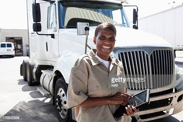 Female truck driver by big rig with digital tablet