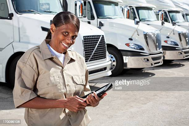 Female truck driver by big rigs with digital tablet