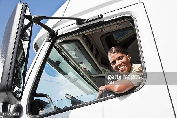Female truck driver sitting in cab of semi-truck