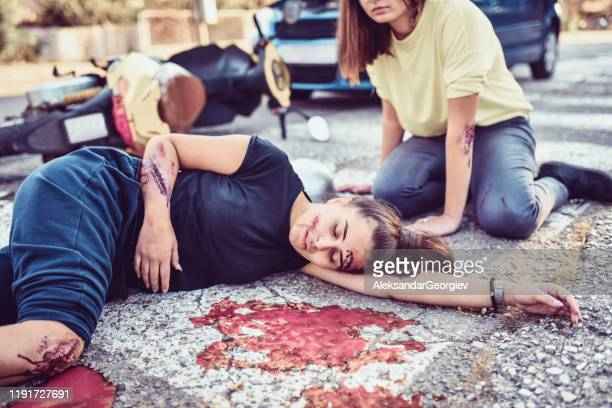 female trying to help unconscious friend in motorcycle accident - gory car accident photos stock pictures, royalty-free photos & images