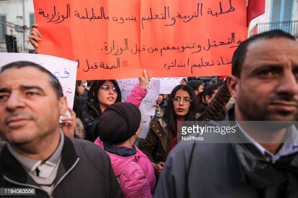 Female Tunisian students raise a placard in protest against the ministry of higher education and scientific research as they attend a gathering held...