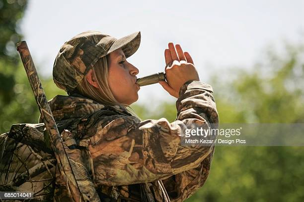 female turkey hunter calling turkey with a turkey call - turkey hunting stock photos and pictures