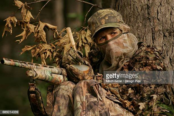 female turkey hunter with shotgun in a turkey blind - turkey hunting stock photos and pictures