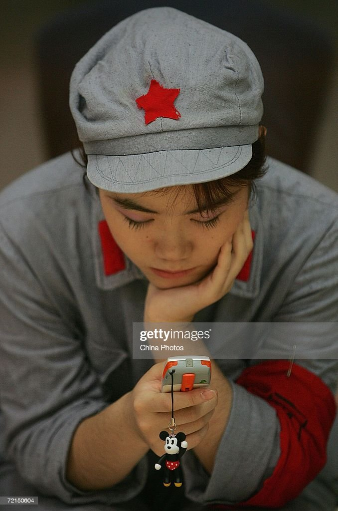 A female undergraduate dressed in Red Army uniform, plays with a cellphone before to come on stage to dance during a ceremony to mark the 70th anniversary of victory of the Long March October 11, 2006 in Beijing, China. The Long March is a massive military retreat undertaken by the Red Army of the Communist Party from 1934 to 1936, to evade the pursuit of the Kuomintang army. The route branched through some of the most difficult terrain of western China and covered about 9,600 km (5,961 miles).