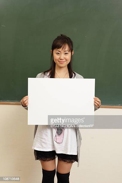 Female university student holding whiteboard