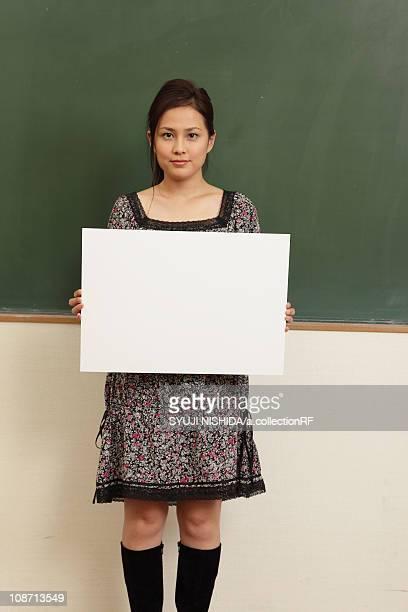 Female university student holding whiteboard