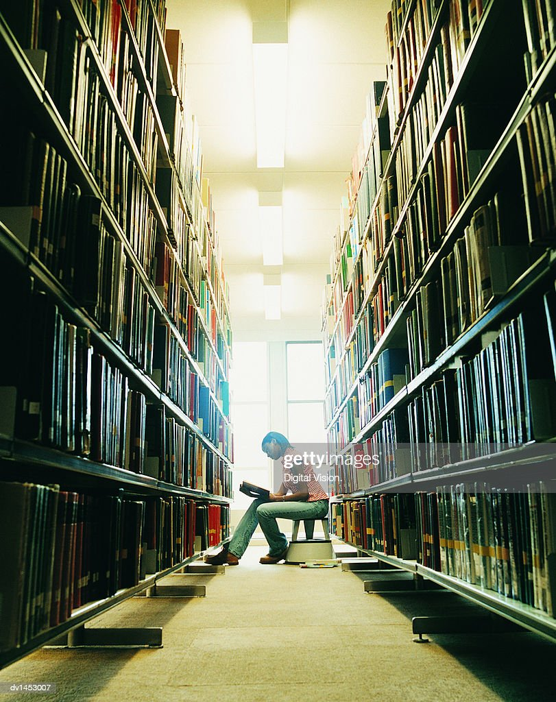 Female University Student Reading a Book in a Library : Stock Photo
