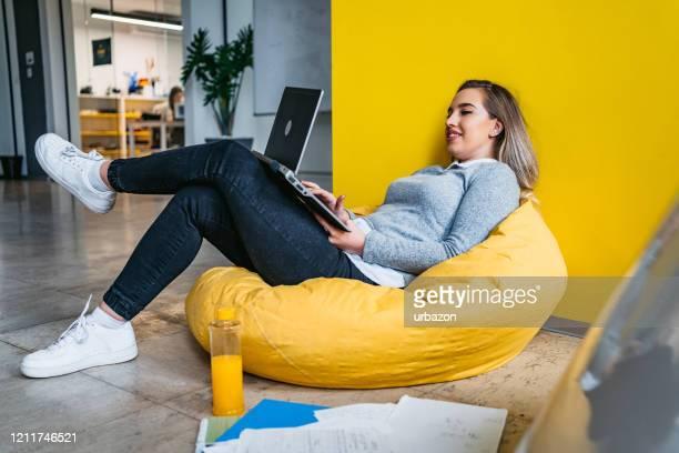 étudiant féminin d'université étudiant dans le sac de haricot sur l'ordinateur portatif - 25 29 ans photos et images de collection