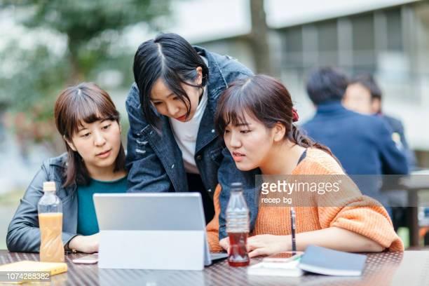 女子大学生のラップトップで一緒に勉強 - 女子大生 ストックフォトと画像