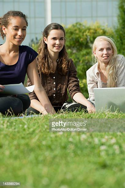 Female university students studying together on grass, low angle view