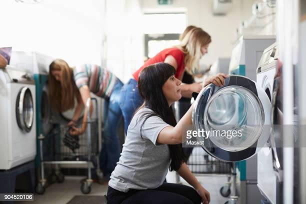 female university students using washing machine at laundromat - waschsalon stock-fotos und bilder