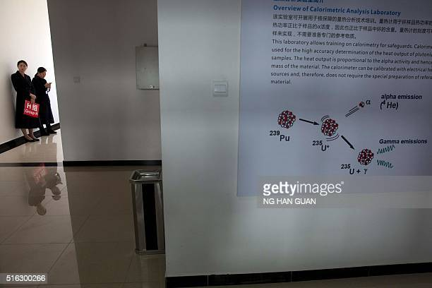 Female ushers wait for guests touring the facilities at the Nuclear Security Center of Excellence in Beijing on March 18 2016 The center constructed...