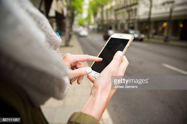 A female using a cell phone for transportation.