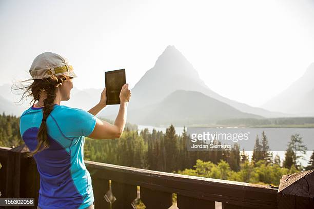 A female using an iPad in the outdoors.