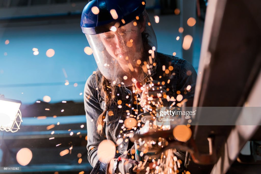 Female using angle grinder in workshop : Stock Photo