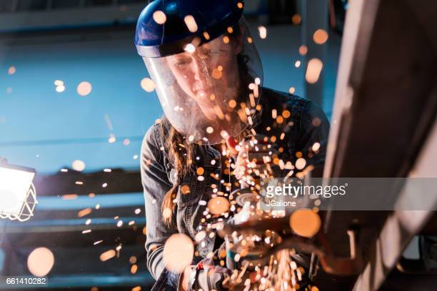 female using angle grinder in workshop - jgalione stock pictures, royalty-free photos & images