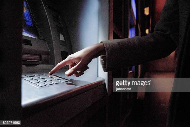 Female using  ATM at night on the street