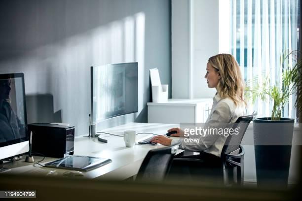 femme utilisant l'ordinateur dans le bureau - chaise de bureau photos et images de collection