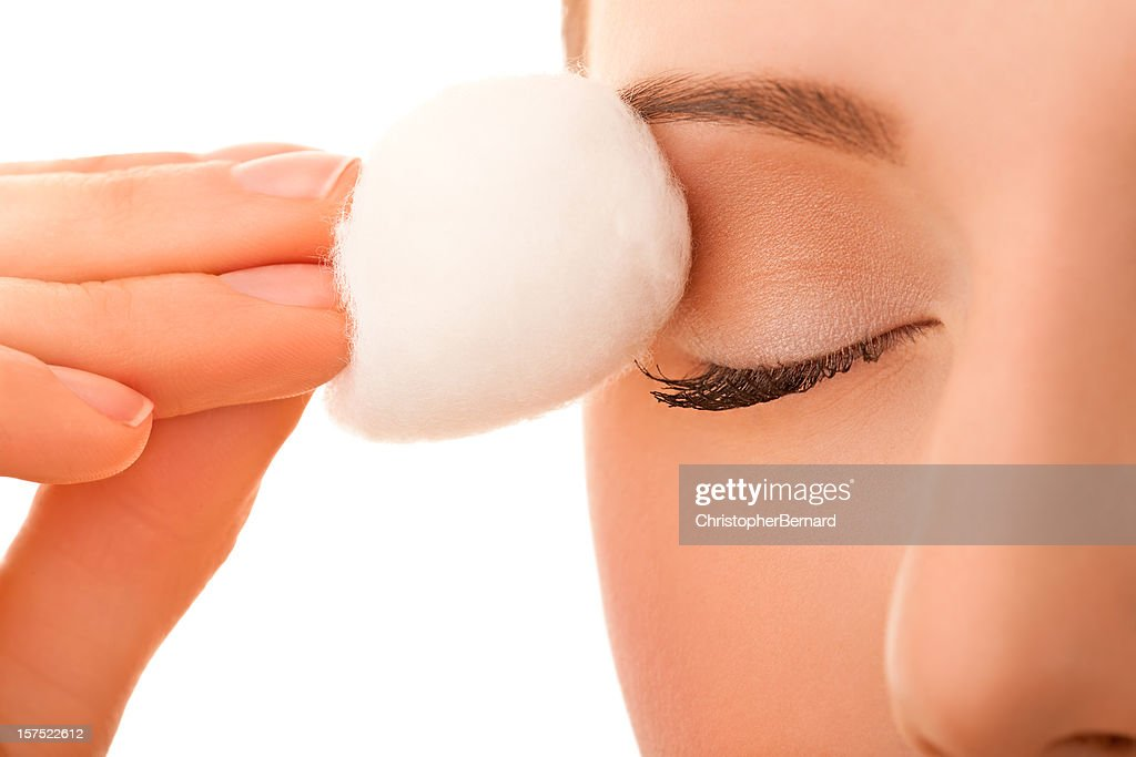 Female using cotton ball to remove eye make-up : Stock Photo