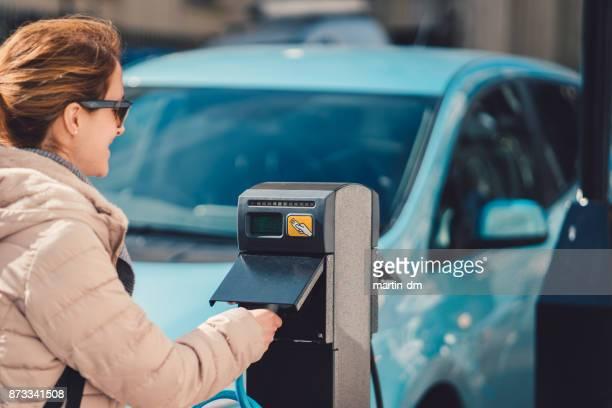 Vrouw met behulp van de elektrische auto-oplader in Verenigd Koninkrijk
