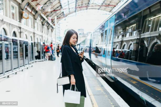 Female using phone at train platform while waiting for the next train