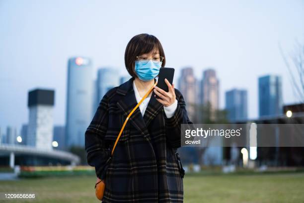 female using smart phone and wearing protective mask in city - south korea stock pictures, royalty-free photos & images