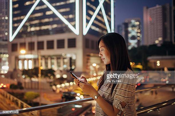 female using smartphone with smile in city - yiu yu hoi stock pictures, royalty-free photos & images