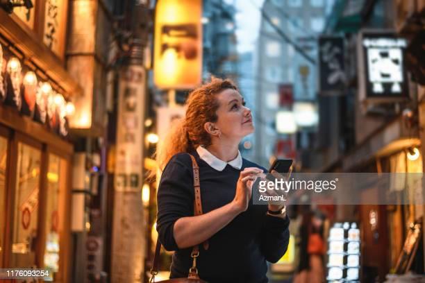 weibliche urlauberin mit smartphone für sightseeing in tokio - shinjuku bezirk stock-fotos und bilder