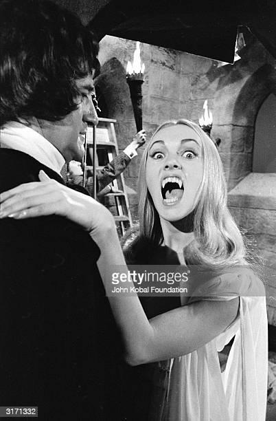 A female vampire played by Ingrid Pitt prepares to sink her fangs into a willing victim in the Hammer horror film 'The Vampire Lovers' directed by...